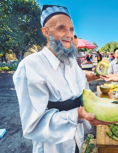新疆麦盖提县央塔克乡维吾尔族瓜农请游客品尝当