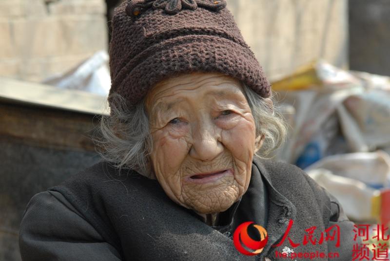 """84岁张小仅:只身照顾两个智障儿子61年   河北省辛集市中里厢乡泊庄村张小仅有两个儿子:61岁的李孟循和45岁的李孟廷。本该享受天伦之乐的老人,却还得照顾两个儿子,因为他们都是智障,没有劳动能力。李孟循每天要干的事情就是出去捡废品。收废品的老人十来天到家里收一次,每次有十来元的收入,但这点收入根本无法支撑这个家。家徒四壁,四处漏风,破旧的被褥已看不清原有的颜色,到处污渍。村支书杨杏礼介绍说,村里已为两个孩子上了""""低保"""",也为老人上了""""五保"""",每季度都过来给他们送一些米面油。同时,为了改善他们的居住环境,村里协调已为他们找了五间房子,让他们搬过去,可老人说什么也不搬。拄着拐杖,已经驼背的她说:""""搬走了,怕我的孩子找不到家。""""一句话让听者泪流满面。"""