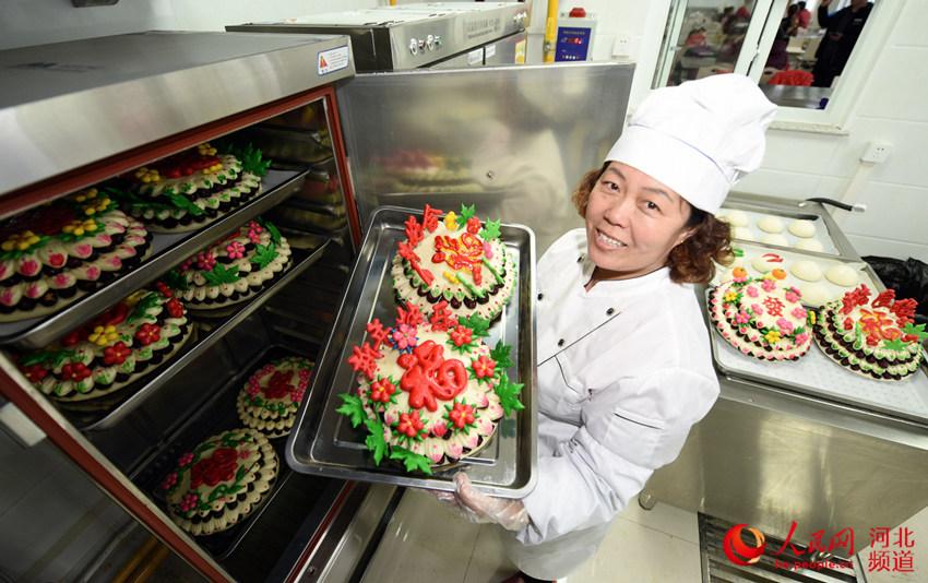 图为村民李会青正在从蒸炉里端出蒸熟的花糕。