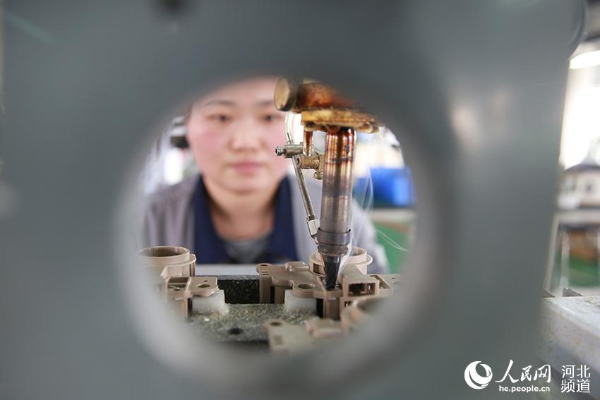 图为工人在生产车间对汽车发电机电压调节器芯片产品进行焊接。