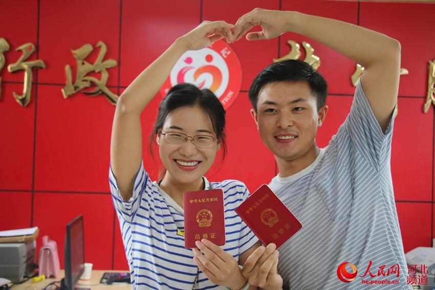 图为8月7日,在河北省广平县民政局婚姻登记处,一对新人领取结婚证后在颁证大厅拍照留念。程学虎摄
