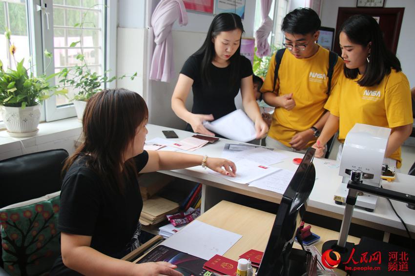 图为8月7日,在河北省广平县民政局婚姻登记处,一对对新人前来领取结婚证。程学虎摄
