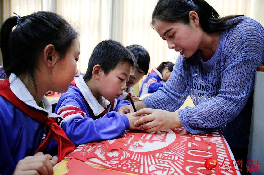 图为广平县广平小学学生在剪纸艺术课上跟着老师创作国庆剪纸作品。