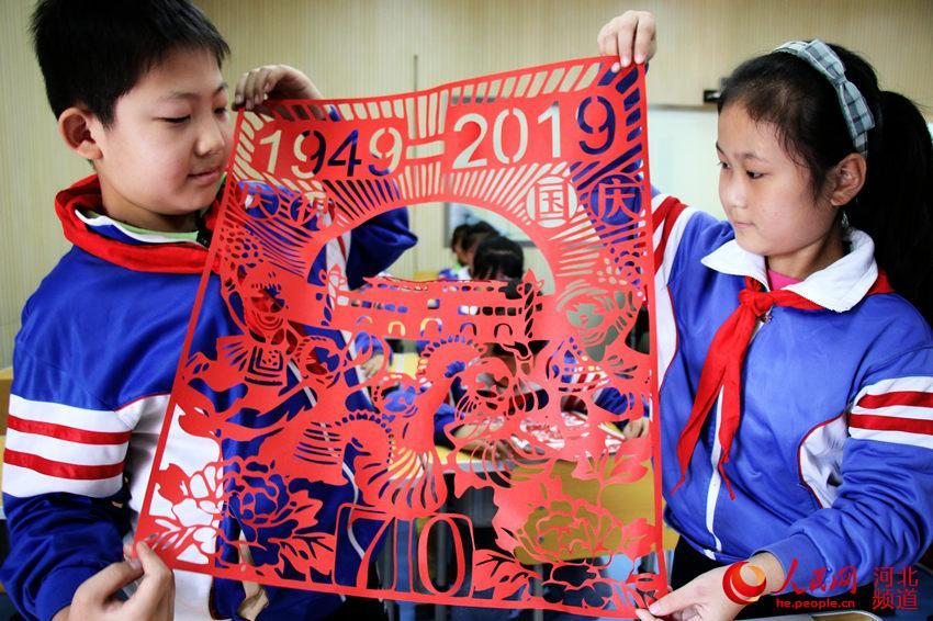图为广平县广平小学学生展示创作的国庆剪纸作品。