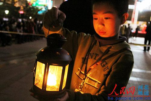 朱娜摄 石家庄/图为石家庄小朋友手捧蜡烛宣传低碳,为地球祈福。朱娜摄